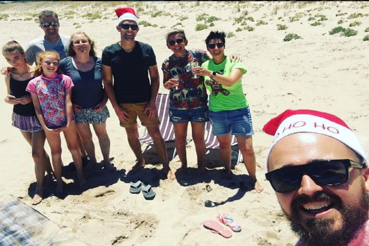 group of people celebrating christmas at the beach at Golden Bay