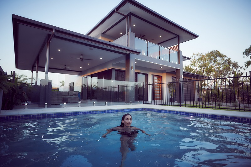 house and woman in pool