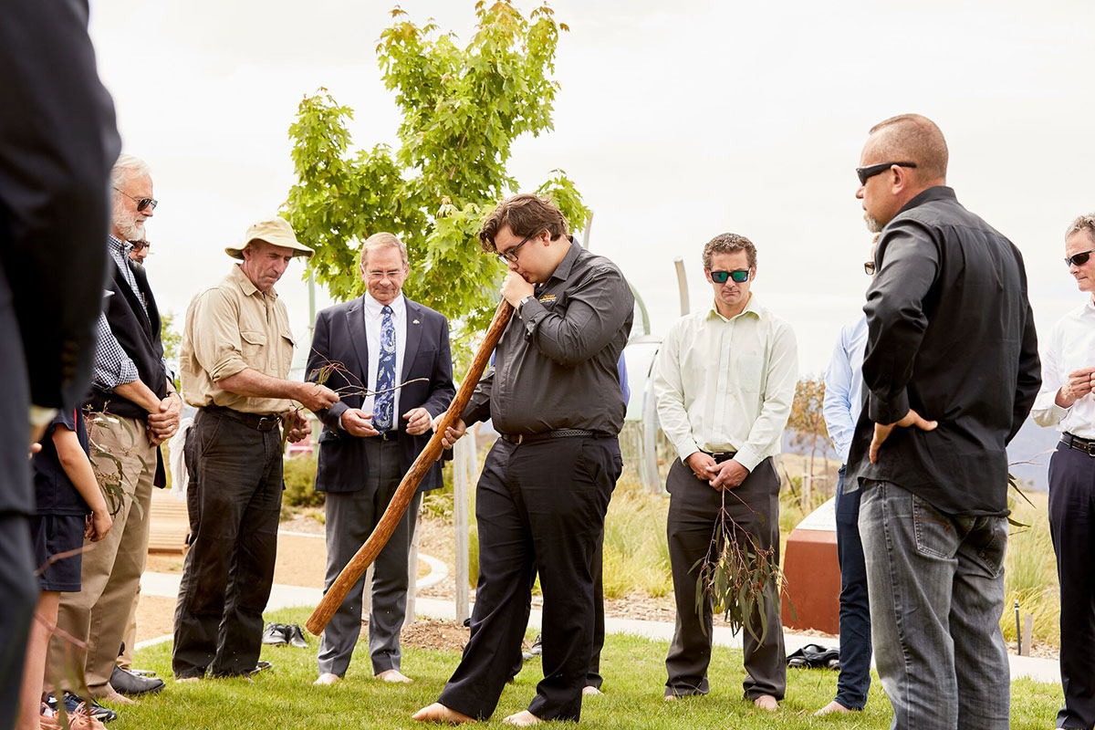 Didgeridoo player Jayden Goodrem performs as guests, including Mayor Tim Overall and Councillor Pete Harrison, cleanse themselves with gum leaves in a barefoot ceremony